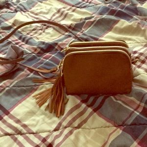 A brown purse with three pockets